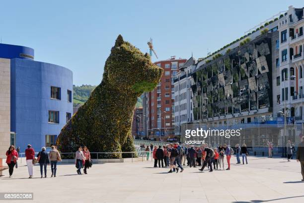 People by Guggenheim Bilbao main entrance with Jeff Koons 'Flower dog'