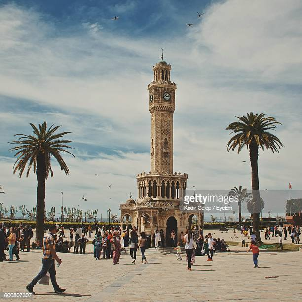 people by historic izmir clock tower against sky - izmir stock pictures, royalty-free photos & images