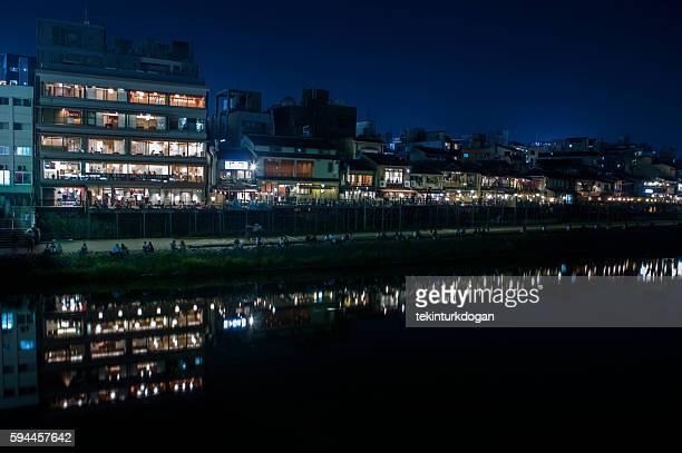 people by kamo river riverbank during night at kyoto japan - fluss kamo stock-fotos und bilder