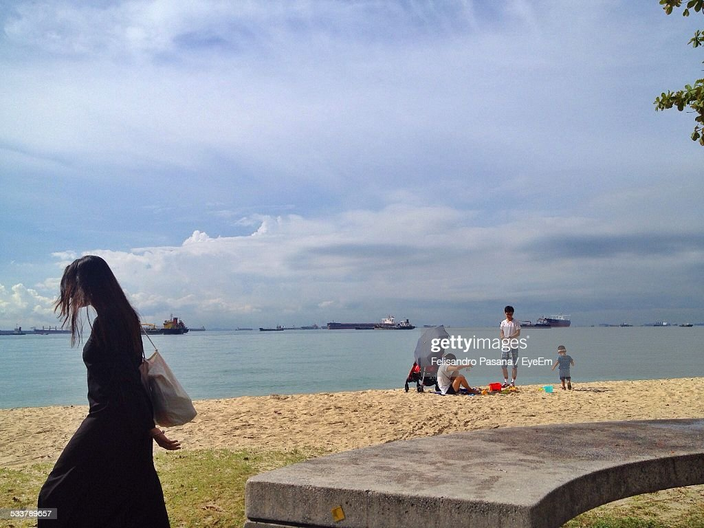 People By Lake Against Cloudy Sky On Sunny Day : Foto stock