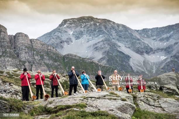 People by mountain playing alphorn, San Bernardino, Ticino, Switzerland, Europe