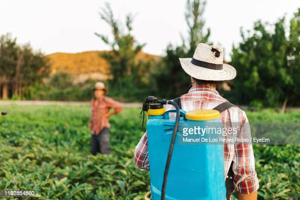 people by plants in farm - crop sprayer stock pictures, royalty-free photos & images