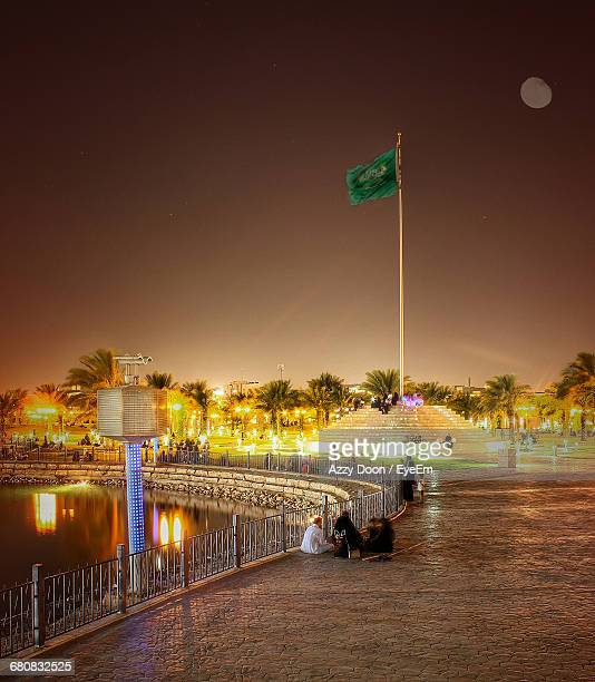 people by pond against saudi arabian flag at illuminated park - saudi arabian flag stock photos and pictures