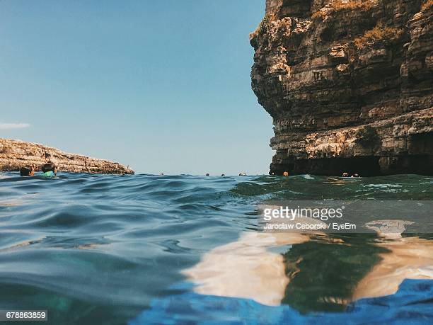 People By Rock Formation In Sea Against Sky