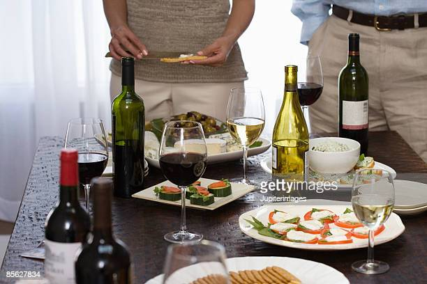 People by table spread of wine and appetizers