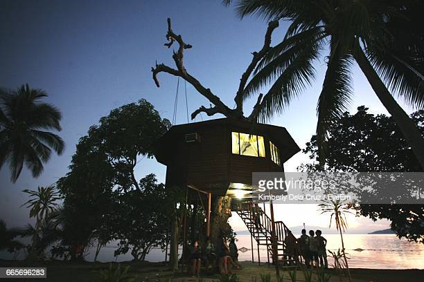 People By Tree House At Beach During Sunset