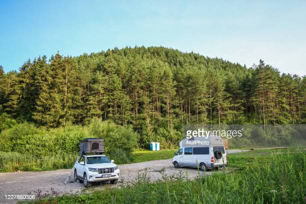 People camping in a 4x4 Toyota Landcriuser with a roof tent and Mercedes Sprinter James Cook edition camper van near the thermal lake Kalameny are...