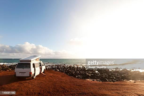 People camping in a van near the ocean.