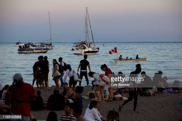 People canoe in Lake Ontario as beachgoers enjoy the last light of the day during Canada Day on July 1 2019 in Toronto Canada Canada Day commemorates...