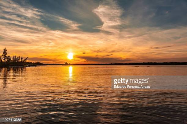 people canoeing and kayaking and the sun setting over the waters of margaret lake - lake sunset stock pictures, royalty-free photos & images