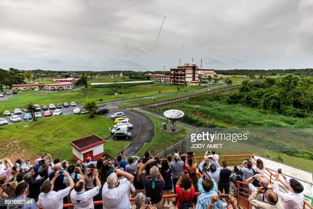 People capture images as an Ariane 5 rocket blasts off from the Kourou Space Centre carrying four Galileo satellites on December 12 in Kourou French...