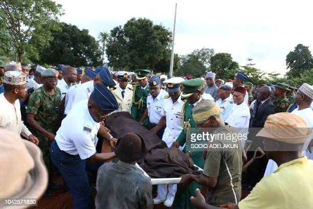 People carries the remains of the two Air Force pilots killed in a fighter jet crash in Abuja on September 28 2018 during their funerals Nigeria's...