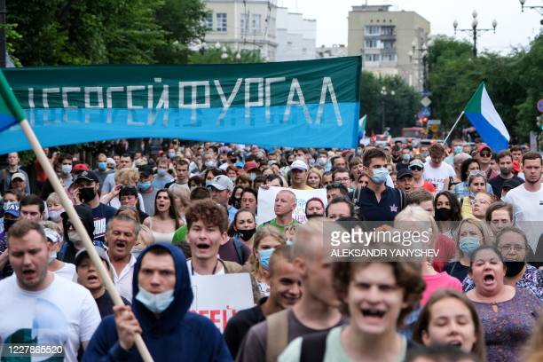 People carry a banner reading Sergei Furgal during an unauthorised rally in support of Sergei Furgal in the Russian far eastern city of Khabarovsk on...