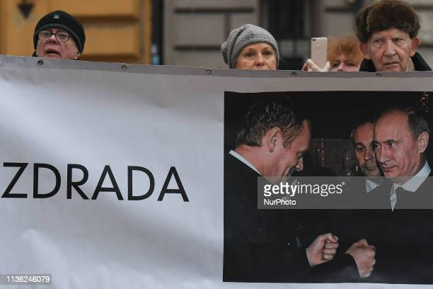 People carry a banner 'Treason' with an image of Donald Tusk and Vladimir Puttin during a procession from Wawel Castle to Katyn Cross monument after...