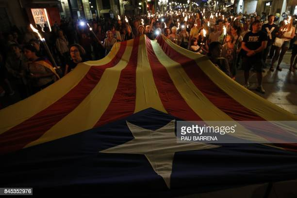"""People carry a big """"Estelada"""" as they march holding torches through the streets of Barcelona during a pro-independence demonstration, on September 10..."""