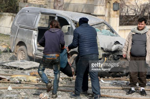 People carry a body of a man around the wreckage site after the consecutive bomb attacks with two bombladen vehicles in Idlib city centre Syria on...