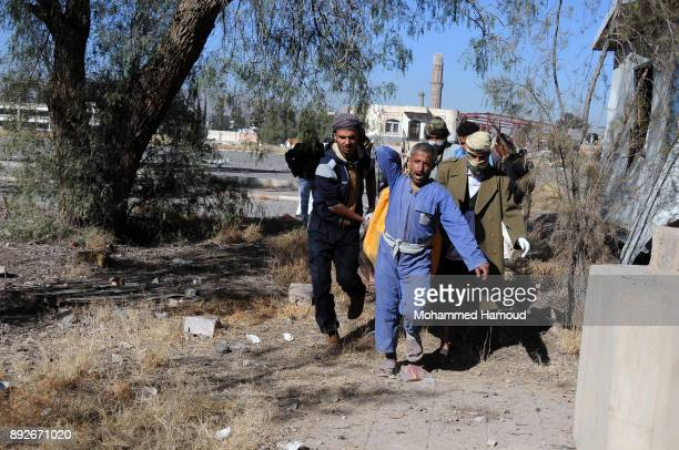 People carry a body of a prisoner after he was killed in airstrikes targeted the prison on December 13 2017 in Sana'a Yemen More than 12 prisoners...