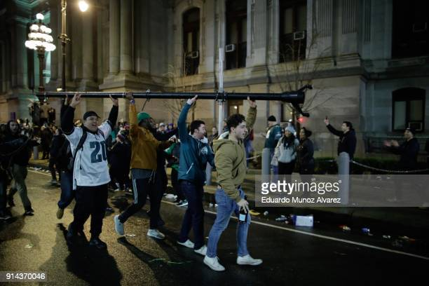 People carry a broken pole while celebrating the Philadelphia Eagles victory in Super Bowl LII game against the New England Patriots on February 5...