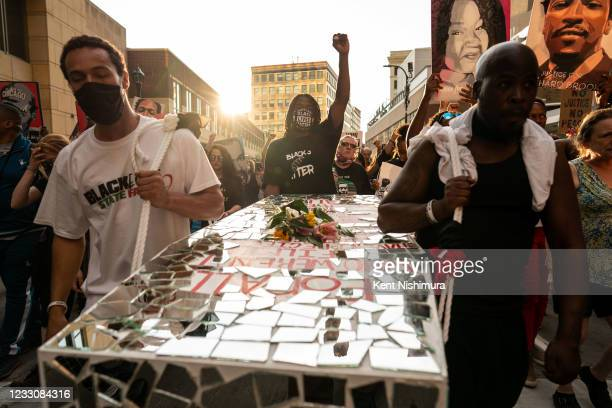 People carry a coffin art piece by Visual Black Justice during the inaugural remembrance rally and march hosted by the George Floyd Global Memorial,...