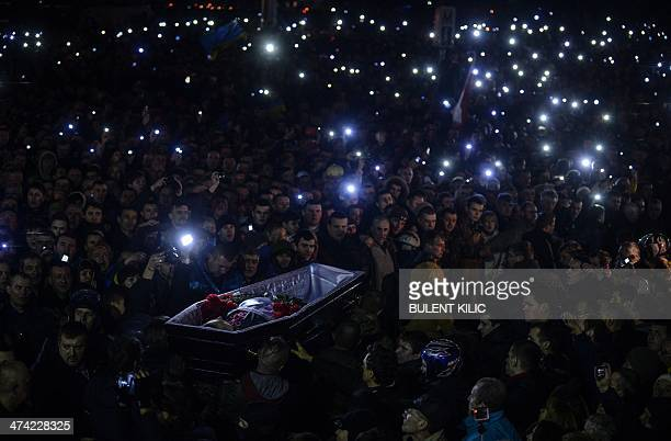 People carry a coffin of a man who was killed during recent clashes as they gather at Independence Square on February 22 2014 Newly freed Ukrainian...