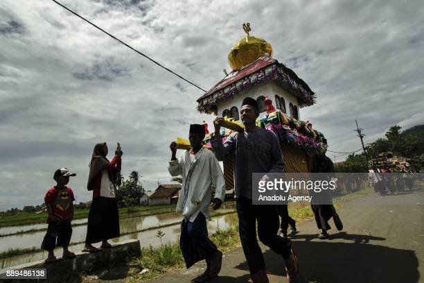 People carry a Dongdang an ornamental basket containing crops food and money as a part of mawlid alNabi celebrations in Comongkor village of...
