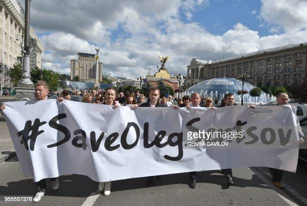 People carry a giant banner with an appeal to free Ukrainian film director Oleg Sentsov during a rally in Kiev on July 1 to demand the release Oleg...