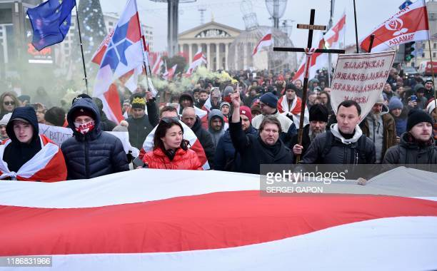 People carry a giant Belarusian historical whiteredwhite flag and antiintegration banners as they attend an opposition rally against a...