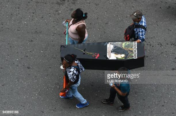 TOPSHOT People carry a makeshift coffin representing a victim during the commemoration of the National Day of Memory and Solidarity with the Victims...