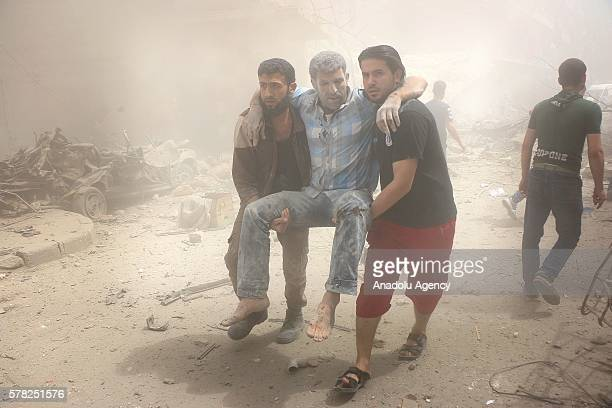 People carry a man after Syrian regime airstrikes targeted the Meshed neighborhood of Aleppo Syria on July 21 2016