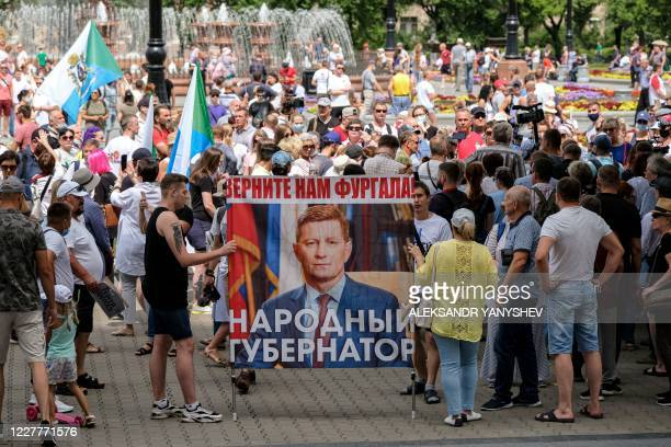 People carry a portrait of Sergei Furgal the governor of the Khabarovsk region during an unauthorised rally in his support in the Russian far eastern...