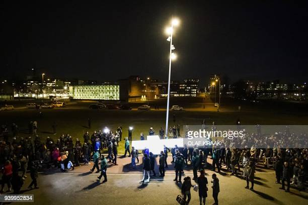 People carry a white cross during a broadcast procession of 'The Passion' by Dutch TV Evangelical Broadcasting through De Bijlmer district in...