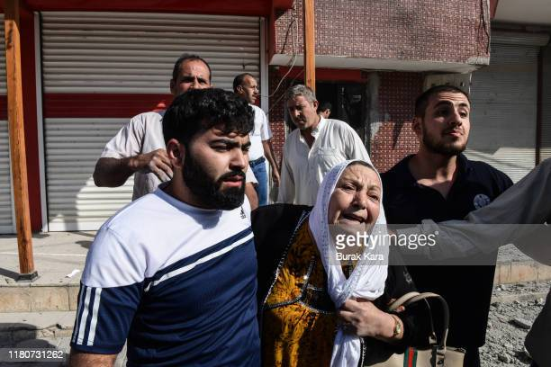 People carry a woman out from her home after a mortar fired from Syria struck her house on October 13 2019 in Akcakale Turkey The military action is...