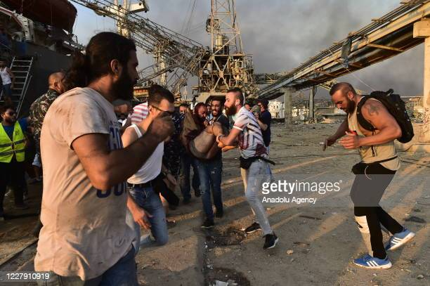 People carry a wounded man after a fire at a warehouse with explosives at the Port of Beirut led to massive blasts in Beirut, Lebanon on August 4,...