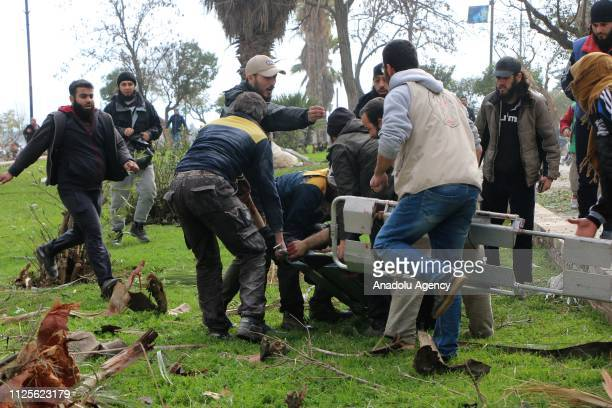 People carry a wounded man around the site after the consecutive bomb attacks with two bombladen vehicles in Idlib city centre Syria on February 18...