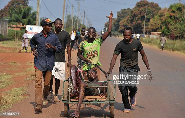 People carry a wounded man in a trolley after an attack by antiBalaka fighters on January 22 2014 in the Pk 13 district north of Bangui The Central...