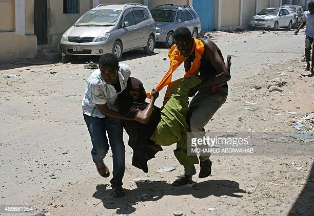 People carry a wounded person at the scene of a car bomb outside the Education Ministry in Mogadishu on April 14 2015 Somalia's AlQaedalinked Shebab...