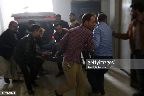 People carry a wounded person to a sahra hospital after Assad regime's warcrafts carried out an airstrike over residential areas of Arbin town of the...