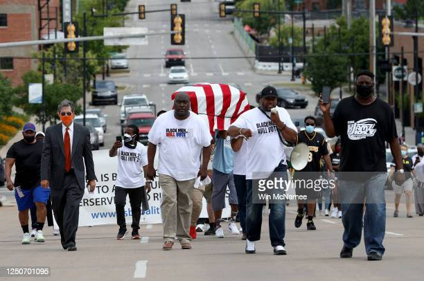 People carry an empty casket draped with an American flag to symbolize the destruction of Tulsa's Black Wall Street in 1921 during a Juneteenth march...
