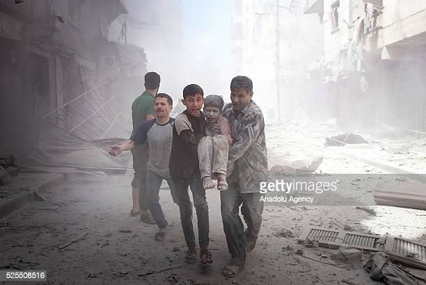 People carry an injured boy after Russian forces staged airstrike over Aleppo's opposition controlled Sukkeri region Syria on April 28 2016