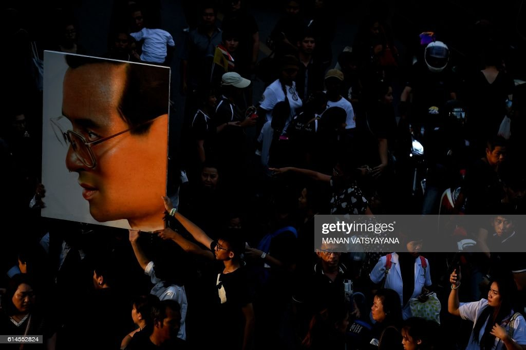 TOPSHOT - People carry away a picture of the late King through a streak of fading sunlight, as thousands line the streets during the procession of Thai King Bhumibol Adulyadej's body to his palace in Bangkok on October 14, 2016. Bhumibol, the world's longest-reigning monarch, passed away aged 88 on October 13, 2016 after years of ill health, removing a stabilising father figure from a country where political tensions remain two years after a military coup. / AFP / MANAN
