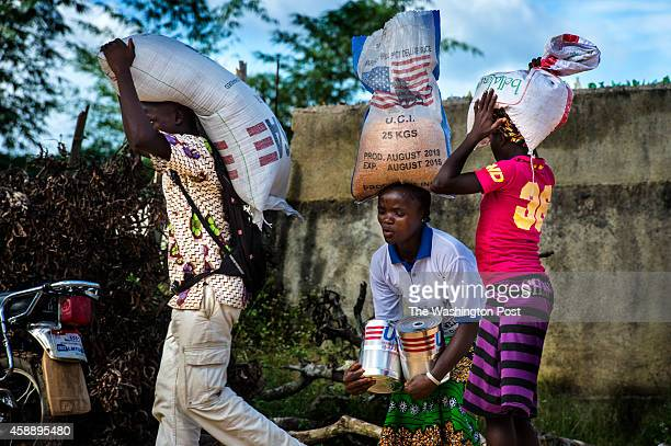 People carry bags of Bulgurwheat and cooking oil after they received a share of food items from WFP's food distribution on Friday November 6 2014 in...