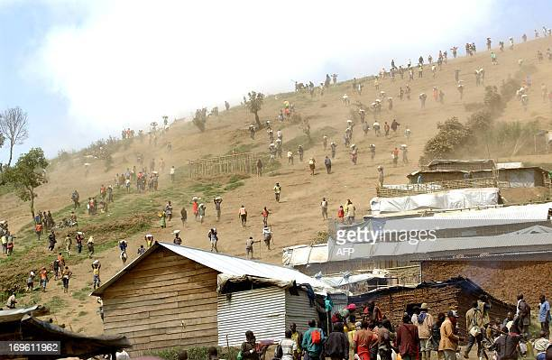 People carry bags of cassiterite coltan which is used in mobile telephones and computers and manganese on May 28 2013 down a hill from the Mudere...