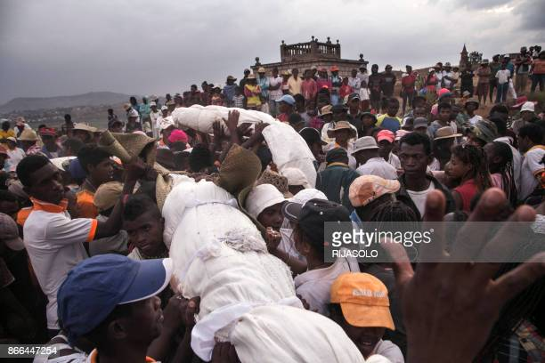People carry bodies wrapped sheets as they take part in a funerary tradition called the Famadihana in the village of Ambohijafy a few kilometres from...