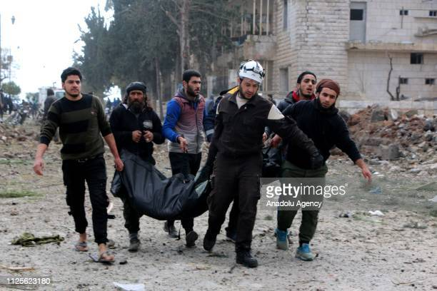 People carry body bag around the site after the consecutive bomb attacks with two bombladen vehicles in Idlib city centre Syria on February 18 2019...