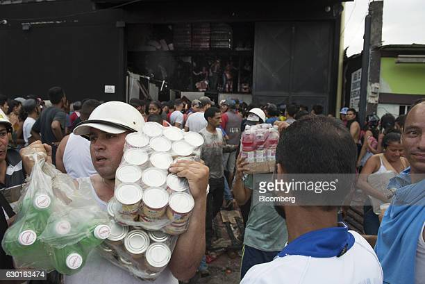 People carry bottles of drinks and cans of sardine as they loot a food warehouse during a protest in La Fria Tachira Venezuela on Saturday Dec 17...