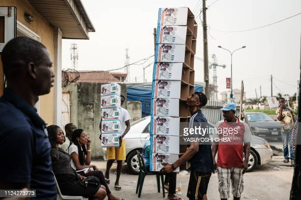 TOPSHOT People carry boxes of food donation bearing the faces of Nigeria's incumbent President Mohammadu Buhari and Vice President Yemi Osinbajo in...