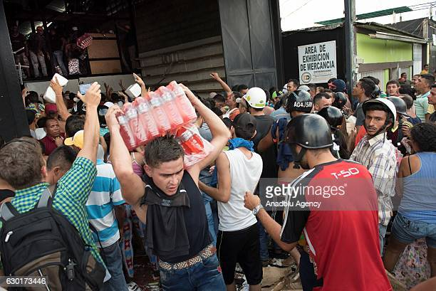 People carry cans of food and bottles of drinks as they loot a food warehouse during a protest in La Fria Tachira Venezuela on Saturday Dec 17 2016