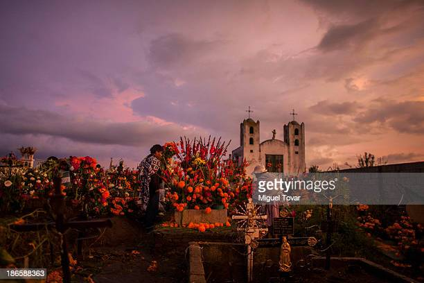 People carry cempasuchil flowers as they arrive at the local cemetery during the Day of the Dead celebration known in spanish as Da de Muertos on...