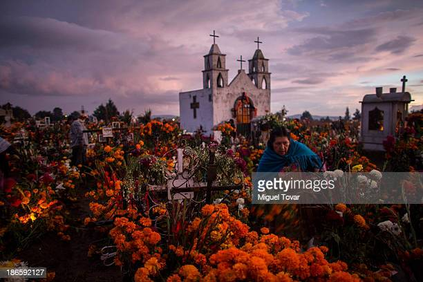 People carry cempasuchil flowers as they arrive at the local cemetery during the Day of the Dead celebration known in spanish as Dia de los Muertos...
