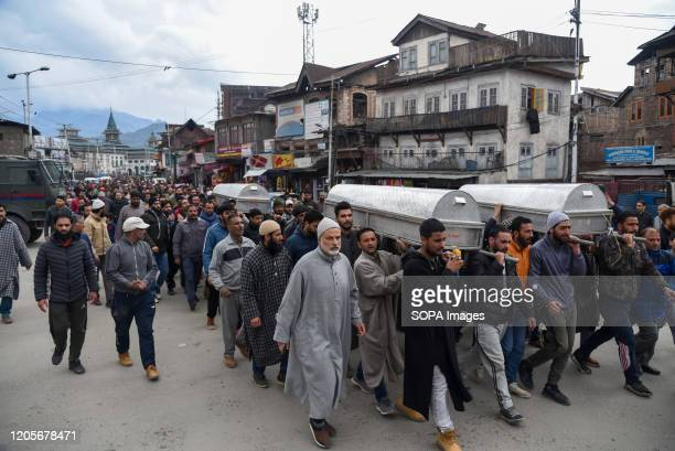 SRINAGAR JAMMU KASHMIR INDIA People carry coffins of the deceased during the aftermath A couple and their threeyearold daughter were charred to death...